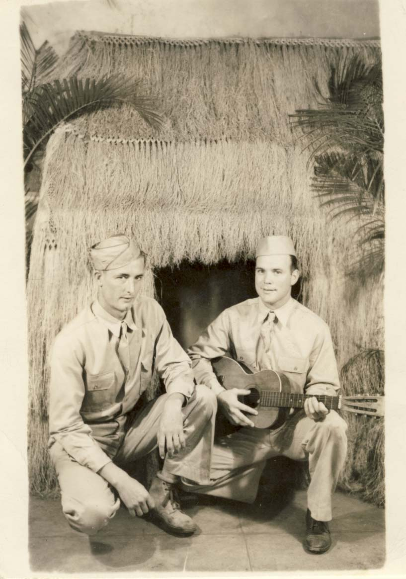 2 men, one with guitar, squatting in front of straw hut photograph