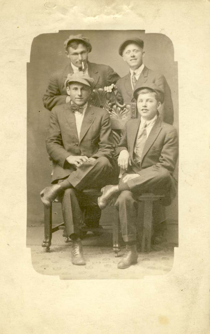 Four young men, two seated in front, all wearing caps postcard