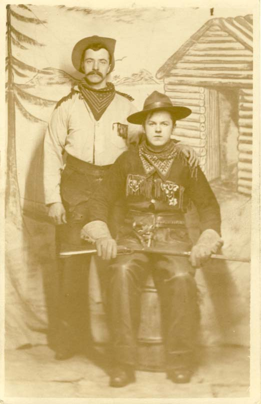 Two men, one standing with hand on the other's shoulder, real photo postcard 1900s