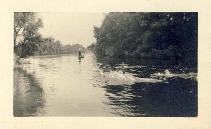 Group of men swimming in a stream photograph